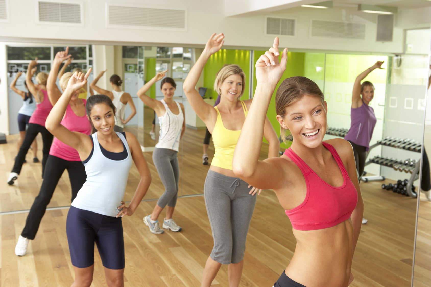 Women Taking Part In Zumba Class In Gym - Hola Mujer